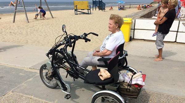 Fietsmaatjes gaste op duofiets bij het strand